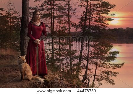 A young woman in medieval clothes with a sword stands beside the river with a Fox against the setting sun
