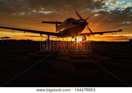 Single-engined business airplane on runway at sunset time. Single turboprop aircraft, plane, small business aircraft on runway.