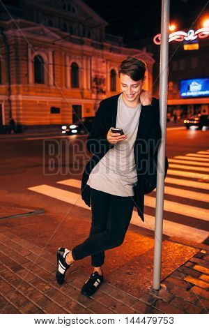Smiling guy with smartphone in night city. Young handsome man standing near lamp post and reading something on his phone in evening street