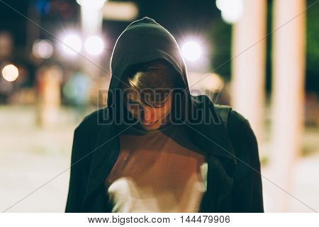 Young handsome man in hood outdoors. Portrait of hooded guy walking through night city