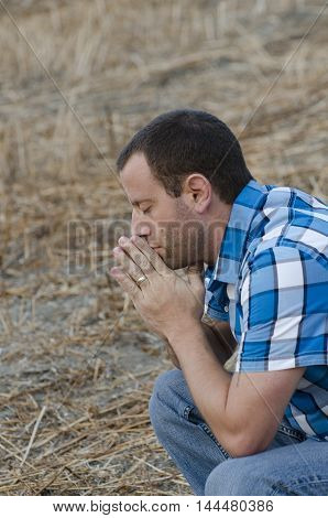Man crouching down and praying with his hands together on a hillside wearing a plaid shirt.