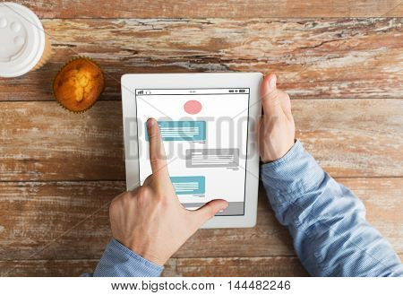 business, online communication, people and technology concept - close up of male hands with messenger on tablet pc computer screen, muffin and coffee cup on wooden table