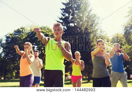 fitness, sport, martial arts, self-defense and healthy lifestyle concept - group of teenage friends or sportsmen exercising and at boot camp