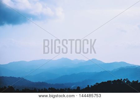 Mountain ridges with silhouette forest in the foreground. Background ridge with spruce forest in the foreground, and layer of hills