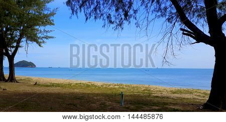 beach shoreline bordered by pine trees, distant ships and Thai longtail boats on a flat sea, Songkhla, Thailand