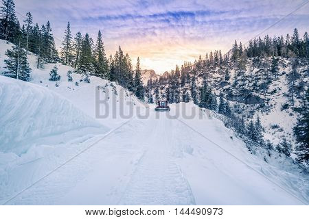 Alpine road mapped out in snow, Austria - Winter mountain landscape with a road being cleared of snow by a snow grooming machine. Image captured in the Austrian Alps mountains Ehrwald municipality.