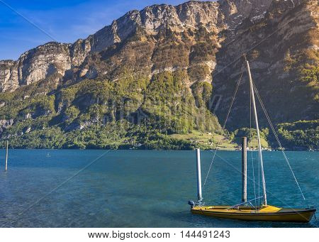 Boat with sails anchored on Walensee lake - Image taken in the Murg Ost village Switzerland presenting a small boat on the Walensee lake in the morning sunlight surrounded by the Swiss Alps mountains.