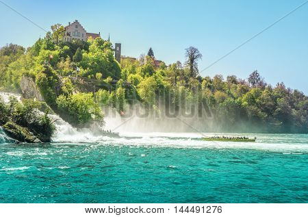 Boats toward Rhine Fall - Boat enters the cloud of vapors made by the falling of the Rhine river at the foot of the Laufen castle Switzerland.