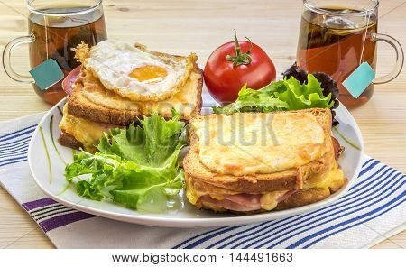 French breakfast for two people - Tasty breakfast for two persons with specific french food croque madame (with egg) and croque monsieur seasoned with fresh salad and tea.