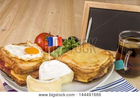 French breakfast and blank chalkboard - Specific french breakfast with melted cheese sandwiches white cheese with the french flag salad cup of tea and a blank chalkboard on a wooden table.