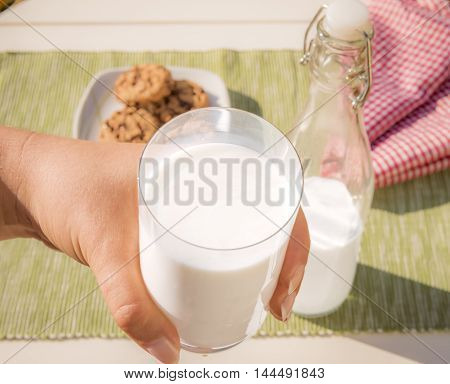 Glass of milk hald in hend - Food photography with a glass of milk held in a woman's hand the bottle of milk and cookies lying on the table in the background.