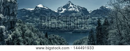 Gloomy panorama with the Swiss Alps peaks - Great panorama over the lake Walensee and its beautiful surroundings the snowy mountain peaks and huge cliffs with dark blue colors added. Picture taken near the village Quinten Switzerland.