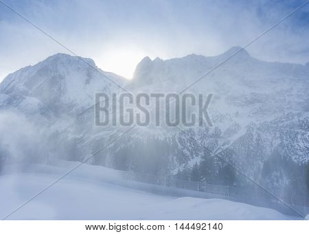 Light snow blizzard in the mountains - Winter alpine scenery with a soft blizzard that blows the fresh snow over the Austrian Alps mountains while the sun is rising over the peaks.