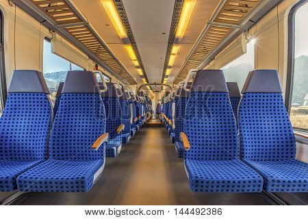 Modern train chairs disposed on two rows - Image with the interior of a german border train. A modern train with comfortable and colorful chairs.