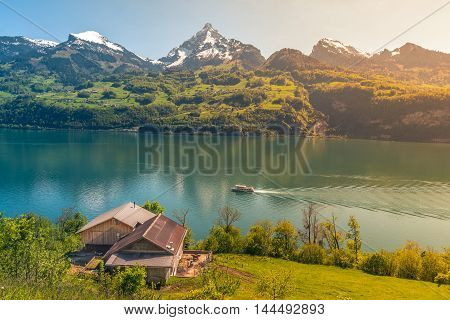 Picturesque alpine scenery warmed up by sunlight - Lovely vacation destination in the Swiss Alps around the Walensee lake. A spring scenery with mountains lake meadows and warm sun.