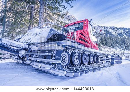 Snow groomer car, on the side view - Side view of a snow groomer vehicle showing details on its tracks with aluminum-steel cleats. Snowmobile used to get ready the alpine ski slopes.