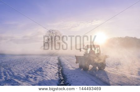 Tractor silhouette on snowy field - Winter landscape with a scene from the rural life warmed up by a splendid sunrise and wrapped in a coat of mist. At the first hours of the morning a farmer starts its work day on a frosted field disturbing the silence o