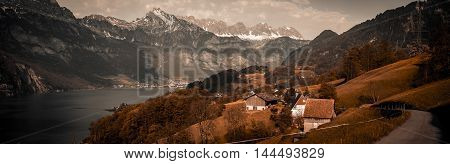 Vintage panorama in Swiss Alps - Vintage panoramic view over the lake Walensee and the surrounding hills and villages with the Swiss Alps in background and a dramatic gray sky. Picture taken in the village Unterterzen Switzerland.