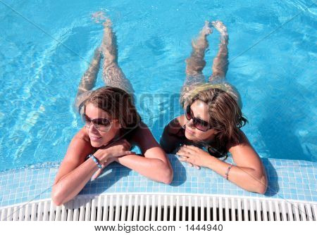 Two Girlfriends Enjoying The Sun Whilst On Vacation Or Holiday