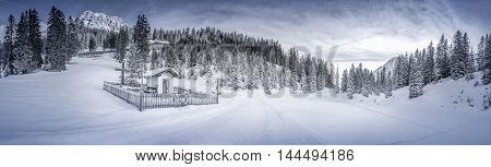 Winter scenery with snowy forest and chapel - Idyllic winter panorama with a snowy forest and a small chapel called