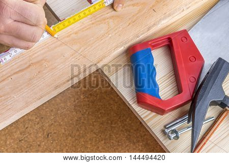 Woodworking and tools close-up Carpentry background image with woodworking tools on the table and a man's hands measuring a wooden board with measuring tape and pencil.