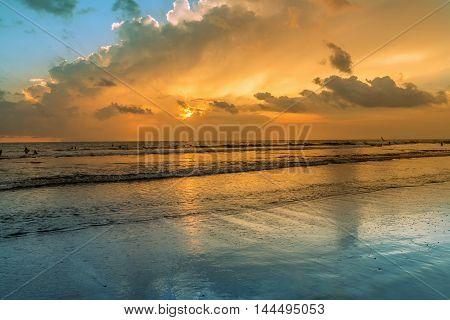 Amazing sunset at Kuta beach, silhouettes of young people at famous sunset beach in Kuta, Bali, Indonesia