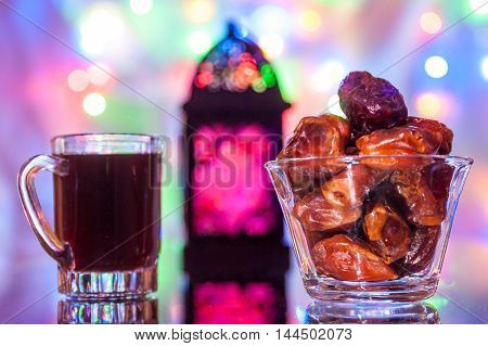 Date fruits in glass tumbler  and glass of tea. Ramadan Eid concept