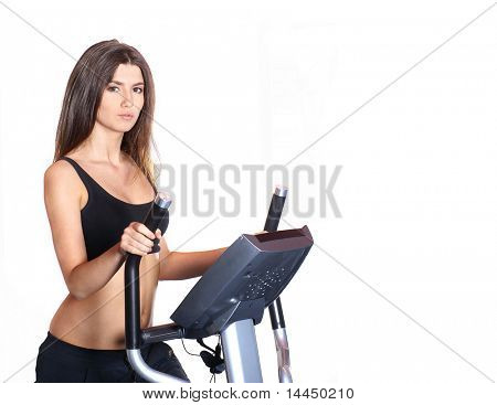 Fit sexy lady on the xtrainer machine isolated on white