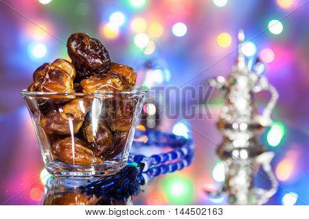 Date fruits in glass tumbler with Muslim prayer beads. Ramadan Eid concept