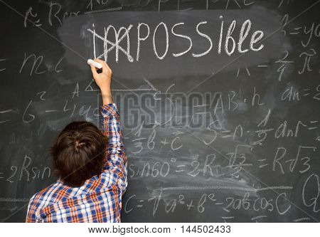 boy putting a cross over impossible on blackboard with math calculations