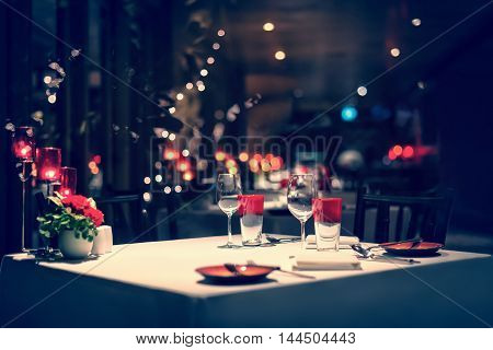 romantic dinner setup red decoration with candle light in a restaurant. Selective focus. Vintage.