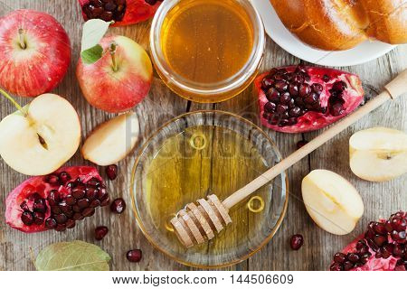 Honey, apple, pomegranate and hala. Table set with traditional food for Jewish New Year Holiday Rosh Hashana