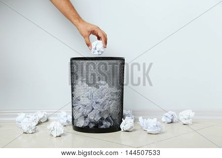 Male hand throwing crumpled paper into metal trashcan