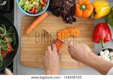 Female hands cutting carrot on wooden board, top view