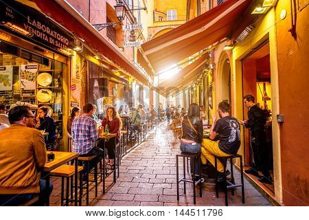 Bologna, Italy - May 23, 2016: People have a lunch on Pescherie Vecchie street near famous italian food markets and shops in the center of Bologna old town. Bologna is gastronomic capital of the Italy