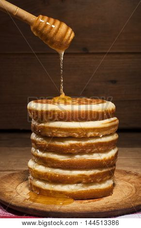 A tall stack of pancakes with dripping honey from drizzler on wooden background.