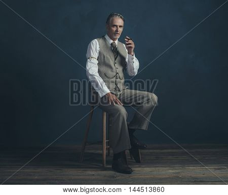 Middle Aged Retro 1920S Man Wearing Suit With Cigar Sitting On Wooden Stool. Empty Room. Vintage Woo