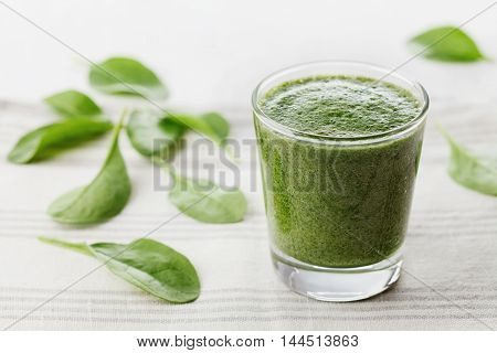 Green spinach smoothie in glass on white table. Detox and diet vegetarian food for breakfast.