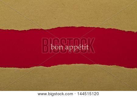 bon appetit written under torn paper .