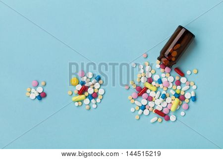 Colorful drug pills on blue background, increasing use and abuse of medication in world concept.