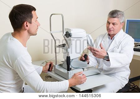 Optometry concept - man having his eyes examined by an eye  elderly doctor.