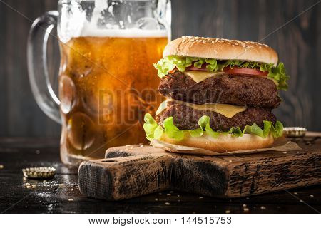 Big hamburger and mug of beer on wooden table