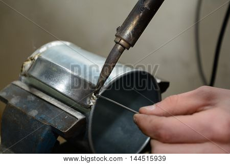 Soldering with solder at a tin can - Close-up