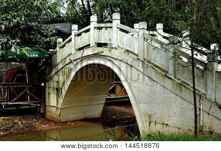 Ping Le China - September 28 2010: White marble Qing Dynasty Jade Belt Bridge (1736-1795 A.D.) relocated from its original site on Kunming Lake at Beijing's Summer Palace