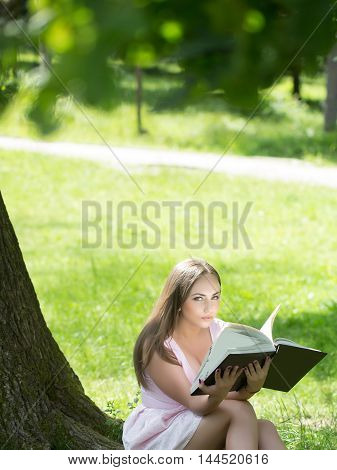young sexy woman with long brunette hair and pretty face sitting on green grass near tree reading book sunny day outdoor on natural background