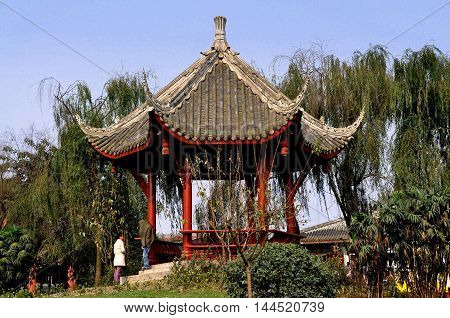 Pixian China - November 3 2009: A hexagonal viewing pavilion with flying eave roofs sits in a small park surrounded by weeping willow trees