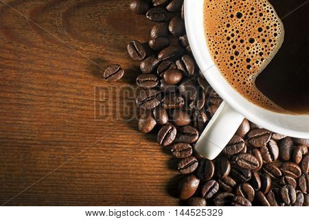 Coffee cup and beans on a wooden background.