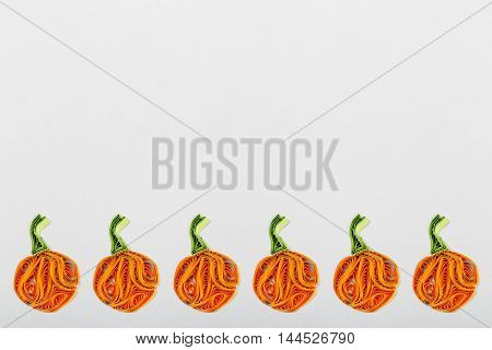 Pumpkins in quilling techniques for Halloween on a light background