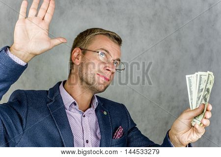 The businessman raised his right hand, left hand holding money on a gray background