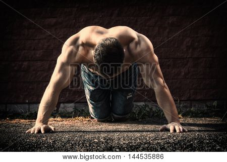 Young fit man showing his muscles -- toned and stylized photo